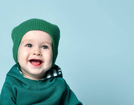 Portrait of a baby in a green hat and hoodie smiling on a green background