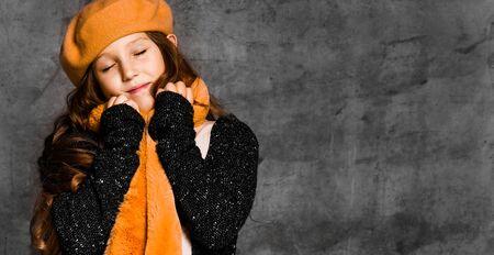 Porträt des jungen lächelnden Mädchenmodells in der stilvollen Freizeitkleidung, im hellen gelben Schal und in der Baskenmütze, die über grauem Betonmauerhintergrund stehen. Trendiges Jugend-Casual-Modekonzept