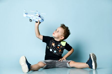 Smiling blond boy in stylish casual clothing sitting on floor with legs streched out and holding toy helicopter present over blue background. Trendy children clothes, holiday gift, party concept