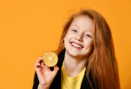 Red-haired teenage child in black jacket and yellow t-shirt. She is smiling, holding half of lemon, posing on orange background. Sincere emotions, fashion, beauty. Close up, copy space