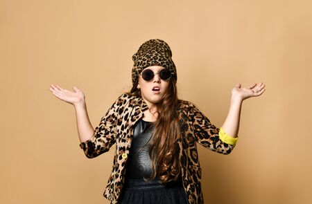 Young plus size girl model in stylish leopard colored casual clothing, black skirt and sunglasses standing and feeling surprised over pastel yellow wall background. Trendy youth fashion concept
