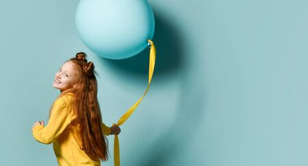 Red-headed teenage girl with fancy hairstyle in yellow sweatshirt holding balloon, posing sideways on blue background. Hipster style, fashion, holiday.