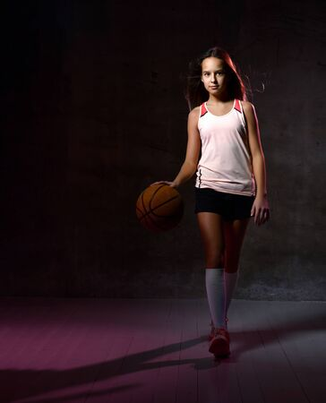 young female basketball player training with ball. Beautiful caucasian woman in sportswear playing basketball on grey background with copy space