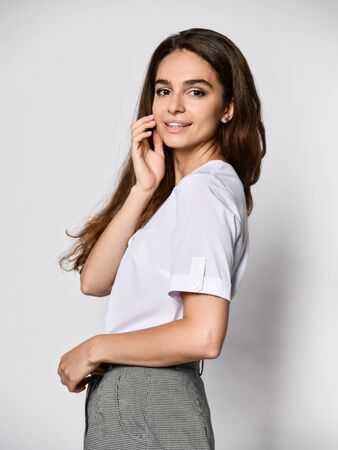 Young beautiful office manager smiles at the camera in a new casual white blouse and classic straight dark skirt on a light background