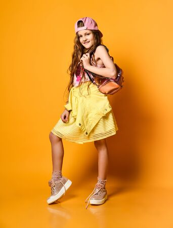 teenager girl in a yellow skirt. sneakers and a cap with a glamorous backpack Childrens fashion concept Stockfoto