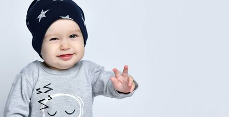 Little baby boy toddler in grey casual jumpsuit, black cap with stars , smiling and gesticulating over white wall background. Trendy baby clothing, happy childhood concept