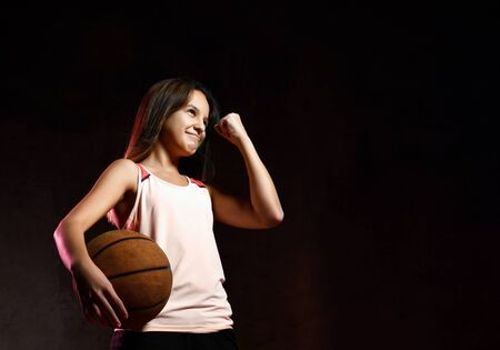 Smiling female basketball player holding a ball, rejoices in victory for a goal scored, in black background