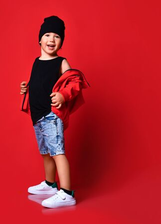 Small positive boy in denim shorts, red jacket, cap white sneakers standing, smiling and looking aside over red wall background. Trendy children clothing and happy childhood concept
