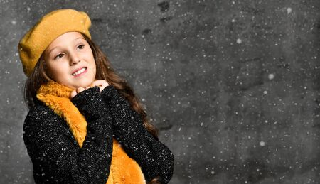 Portrait of young smiling girl model in stylish casual winter clothing and bright yellow accessories over grey concrete wall background with snowflakes. Trendy youth casual winter fashion concept Stockfoto