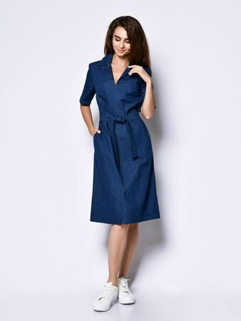 Female model in a blue urban dress-shirt and full-length sneakers. Lovely girl in romantic clothes goes on a date, to the office, to a meeting. Urban fashion.