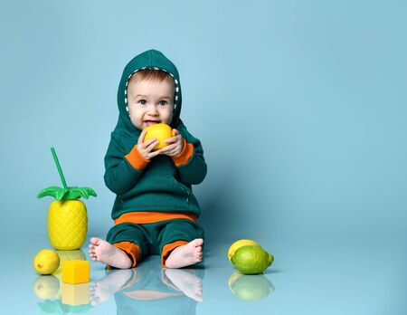 Little baby boy in stylish casual clothing barefoot sitting on floor and licking fresh ripe yellow lemon fruit over blue wall background. Trendy baby clothing, healthy food, happy childhood concept