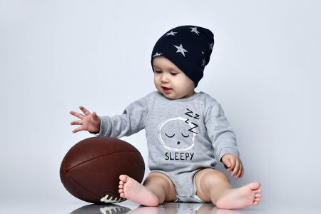 Little baby boy toddler in grey casual jumpsuit, black cap with stars and barefoot sitting on floor with rugby ball over white wall background. Trendy baby clothing, happy childhood concept