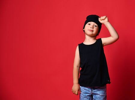 Small positive boy in stylish casual clothing and cap standing and smiling over red wall background. Guy thinks about something nice