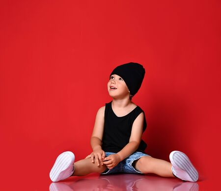 Small positive boy in stylish casual clothing, cap and white sneakers sitting on floor, looking up and smiling over red wall background. Trendy children clothing and happy childhood concept Stockfoto