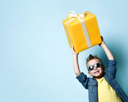 Smiling blond boy in stylish casual clothing and sunglasses holding big yellow present box in raised hands over blue background. Trendy children clothes, holiday, party concept
