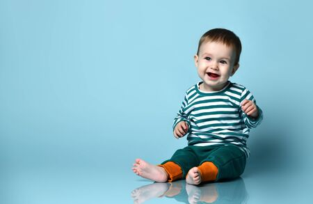 Little baby boy in stylish casual clothing barefoot sitting on floor and smiling over blue wall background. Trendy baby clothing and happy childhood concept