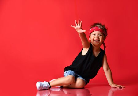 Small happy boy in stylish casual clothing, red hair bandana and white sneakers sitting on floor and smiling over red background. Trendy children clothing, happy childhood concept Stockfoto