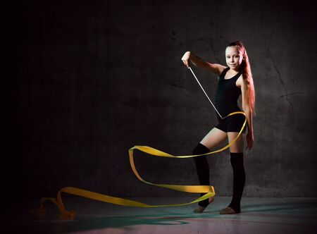 portrait of beautiful young brunette woman gymnast training calisthenics exercise with yellow ribbon on dark smoke studio background. Art gymnastics concept