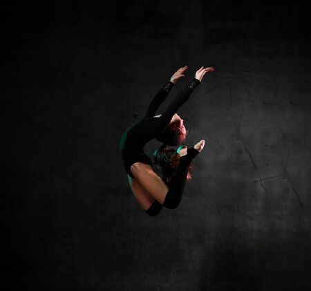 Cool sporty girl gymnast in black sport body and uppers jumping and making dymnastic pose in air over dark background. Rhytmhic gimnastics beauty cocnept