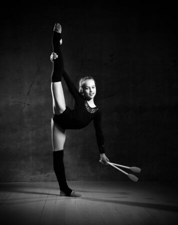Balck and white phoro of girl gymnast in black sport body and uppers standing sideways and holding two pink gymnastic maces over dark background. Rhytmhic gimnastics beauty cocnept Stockfoto