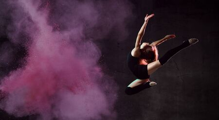 Young girl gymnast in black sport body and uppers making circle in jump over dark background with colorful smoke. Rhythmic gymnastics beauty concept