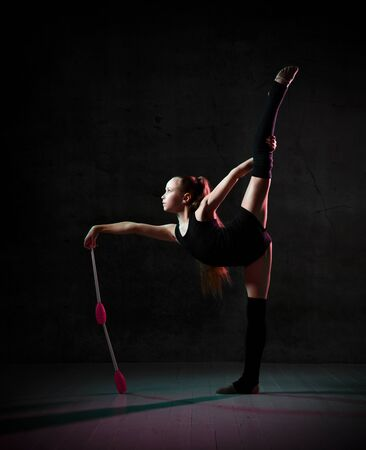 young gymnast girl in a black bodysuit makes a stand on one leg, leaning on two clubs placed one on the other. on a dark concrete background.