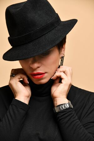 Portrait of middle-aged woman in black hat worn to one side, black poloneck and earings over dark yellow wall background. Trendy accessories, fashion and beauty concept Stockfoto