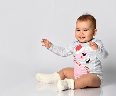 Little kid in socks and gray bodysuit with christmas flamingo print. She is sitting on the floor isolated on white. holidays. Articles about childhood or advertising for babies. Close up Stockfoto