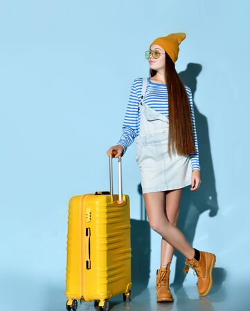 Adolescent in jeans overall skirt, striped sweatshirt, sunglasses, boots and hat. She posing cross-legged with yellow suitcase, blue background. Hipster style, fashion, beauty. Copy space. Full length