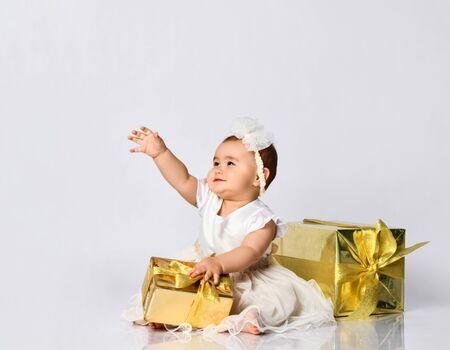 Toddler in dress, headband, barefoot. She raised hand, smiling, holding golden gift box, sitting on floor isolated on white. Christmas, New Year, birthday. Childhood, advertising for babies. Close up