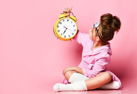 A cute little girl with a dishevelled hairstyle sits on the floor and looks that hour on, on her big yellow clock alarm clock Stockfoto