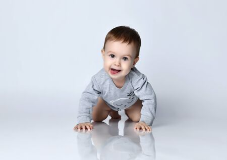 Portrait of little baby boy toddler in grey casual jumpsuit lying on floor, looking at camera and smiling over white wall background. Trendy baby clothing, first steps and happy childhood concept