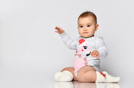 Little child in socks and gray bodysuit with christmas flamingo print. She is sitting on the floor isolated on white. New Year, holidays. Articles about childhood or advertising for babies. Close up