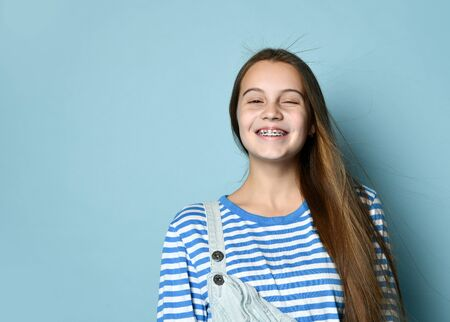 Teenager in jeans overall and striped sweatshirt. She is laughing while posing against blue studio background. Braces on teeth. Sincere emotions, hipster style, fashion, beauty. Copy space. Close up