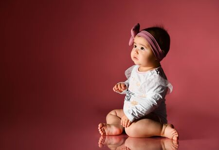 Baby girl in headband and smart white bodysuit, barefoot. She sitting on floor against pink background. New Year, holidays. Articles about childhood, advertising for babies. Close up, copy space