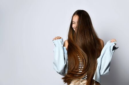 Teenager with long hair, in striped t-shirt and denim jacket. She is laughing, posing isolated on white studio background. Braces on teeth. Sincere emotions, hipster style. Copy space. Close up