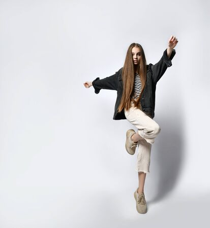 Teen lady with long hair, in striped t-shirt, black denim jacket, beige pants and sneakers. She looking at you, posing isolated on white. Sincere emotions, hipster style. Copy space. Close up Stockfoto