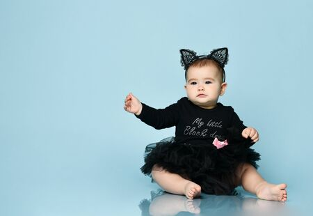 Baby girl in headband in form of cat ears, black bodysuit with pink bow and tutu, barefoot. She sitting on floor against blue studio background. Childhood, advertising for babies. Copy space, close up Stockfoto