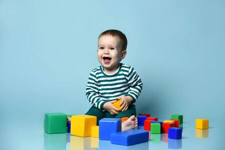 Little baby boy in stylish casual clothing barefoot sitting on floor and playing with colorful toy cubes over blue wall background. Trendy baby clothing, learning and happy childhood concept