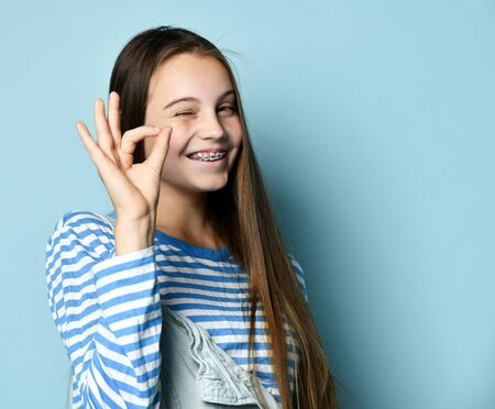 Teenage female in jeans overall, striped sweatshirt. She smiling, showing quiet sign, posing on blue background. Braces on teeth. Sincere emotions, hipster style, fashion, beauty. Copy space. Close up Stockfoto