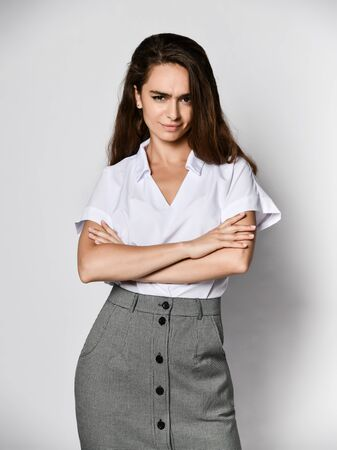 Angry woman office manager clouse her arms over her chest in a new casual white blouse and classic straight dark skirt on a light background Stockfoto