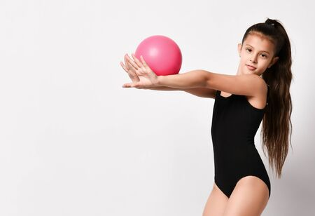 girl gymnast in black body and leggings is training with a pink gymnastic ball. childrens professional sport. Rhythmic gymnastics.