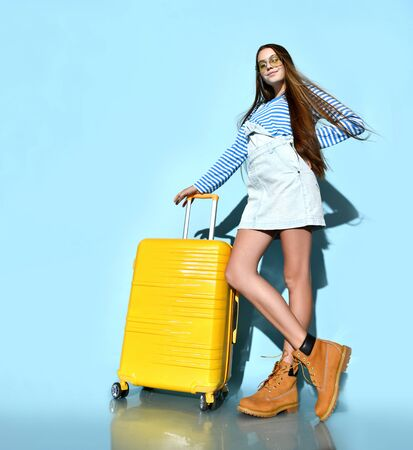 Teenage girl in jeans overall skirt, striped sweatshirt, sunglasses and boots. She smiling, posing with yellow suitcase, blue background. Hipster style, fashion, beauty. Copy space. Full length Stockfoto