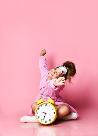 Sweet little girl stretches and yawns after sleep. She is wearing a plush pink robe, a sleep bandage and terry socks. Sitting near the alarm clock on a pink background.