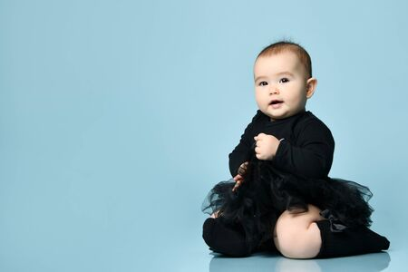 Little kid in black bodysuit with pink bow, poofy skirt and socks. She smiling, sitting on floor against blue studio background. Articles about childhood, advertising for babies. Copy space, close up Stockfoto