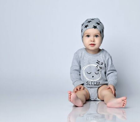 Little baby boy toddler in grey casual jumpsuit, cap and barefoot sitting on floor and smiling with raised hands over white wall background. Trendy baby clothing and happy childhood concept