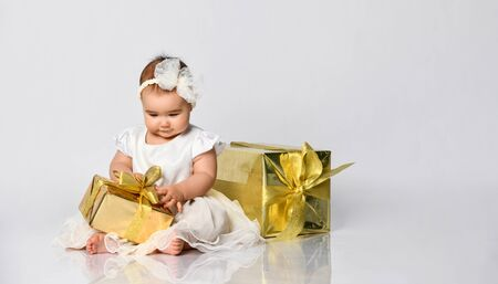 Baby girl in dress and headband, barefoot. She holding golden gift box tied with ribbon, sitting on floor isolated on white. Christmas, New Year, birthday. Childhood, advertising for babies. Close up