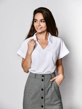 Young beautiful woman office manager posing in a new casual white blouse and classic straight dark skirt on a light background. Looking away