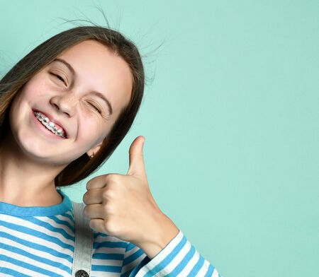 Teenage female in jeans overall, striped sweatshirt. She smiling, showing thumbs up, winking, posing on blue background. Braces on teeth. Sincere emotions, fashion, beauty. Copy space. Close up