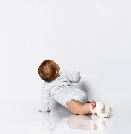 Little kid in gray bodysuit and socks with red bows. She is creeping on the floor, isolated on white. Concept for articles about childhood or advertising for babies. Close up, copy space, back view